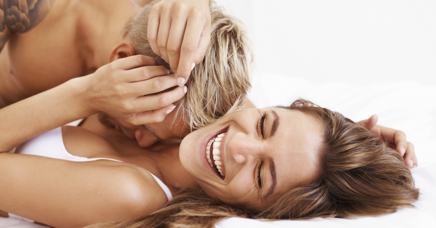 Portrait of couple enjoying together while romancing in bed