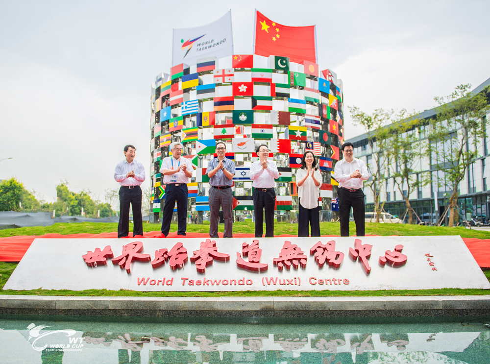 Dr.-Choue-second-from-the-left-is-taking-a-photo-in-front-of-sculpture-with-209-flags-which-represent-each-of-the-WT-Member-National-Associations